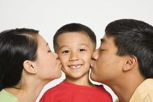 Asian mother and father kissing opposite cheeks of smiling son